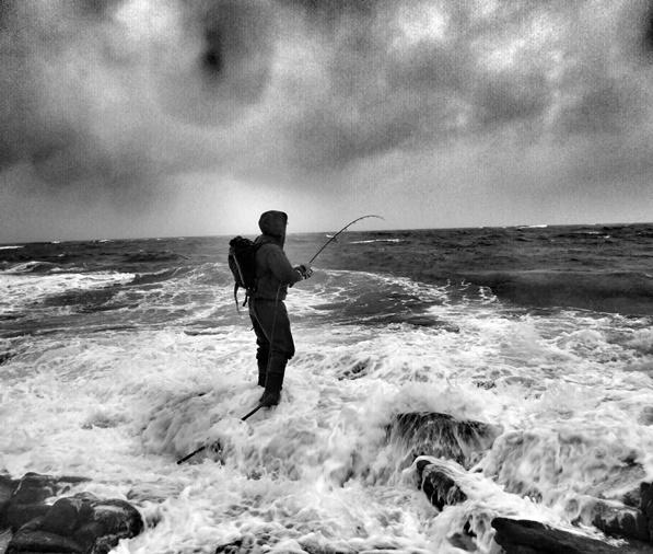 A bass angler facing the sea